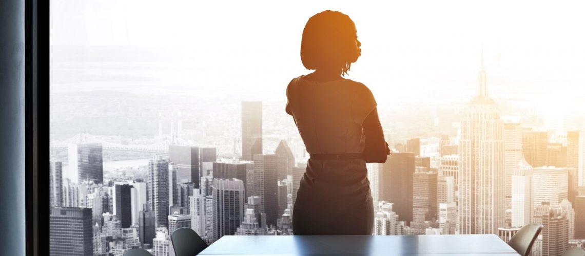 Rearview shot of a young businesswoman looking out from a large window in the office